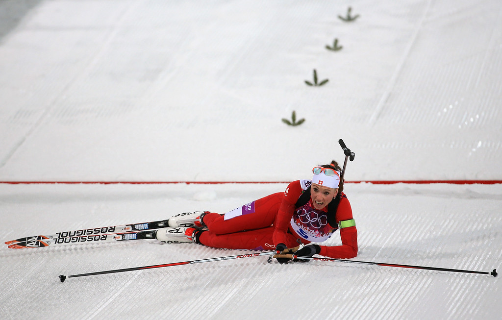 . Selina Gasparin of Switzerland collapses after finishing the Women\'s 12.5 km Mass Start during day ten of the Sochi 2014 Winter Olympics at Laura Cross-country Ski & Biathlon Center on February 17, 2014 in Sochi, Russia.  (Photo by Richard Heathcote/Getty Images)