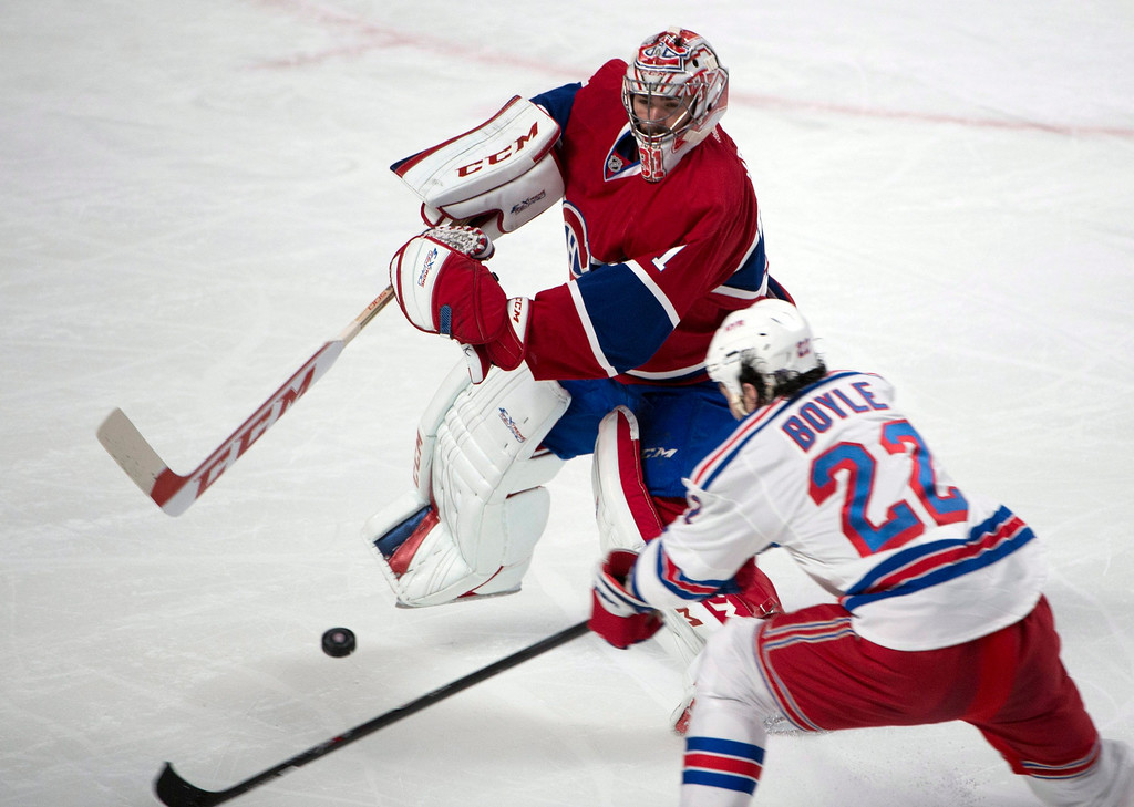 . Montreal Canadiens goalie Carey Price leaves his crease to clear a puck under pressure from New York Rangers center Brian Boyle during the first period in Game 1 of the Eastern Conference finals in the NHL hockey Stanley Cup playoffs in Montreal on Saturday, May 17, 2014. (AP Photo/The Canadian Press, Adrian Wyld)
