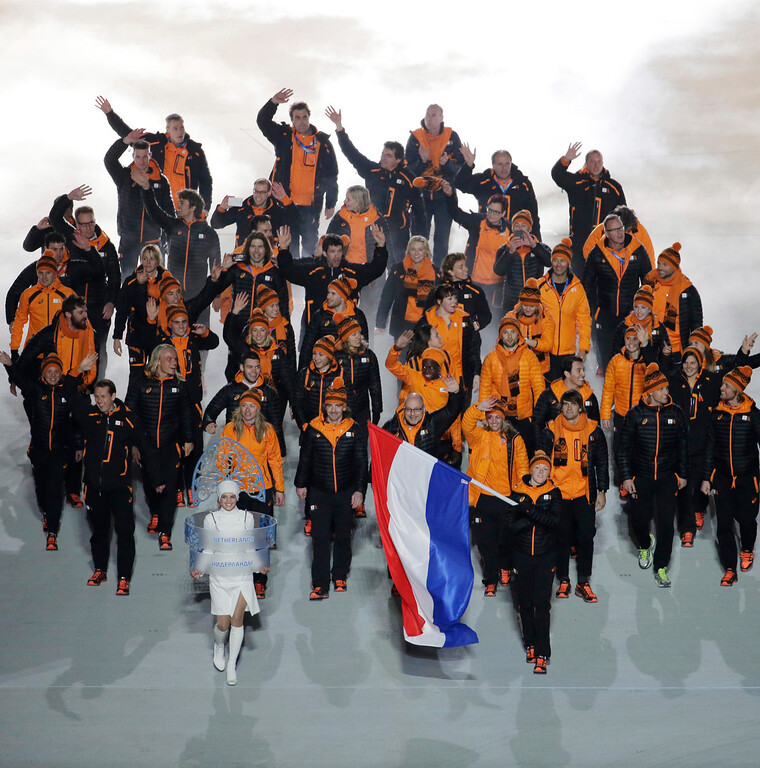 . Jorien ter Mors of Netherlands holds her national flag and enters the arena with teammates during the opening ceremony of the 2014 Winter Olympics in Sochi, Russia, Friday, Feb. 7, 2014. (AP Photo/Charlie Riedel)