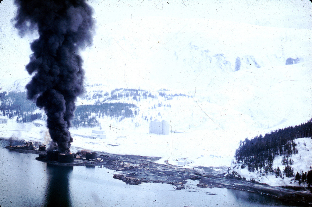 . Alaska Earthquake March 27, 1964. The dock area, a tank farm, and railroad facilities at Whittier were severely damaged by surge-waves developed by underwater landslides in Passage Canal. The waves inundated the area of darkened ground, where the snow was soiled or removed by the waves. U.S. Geological Survey photo