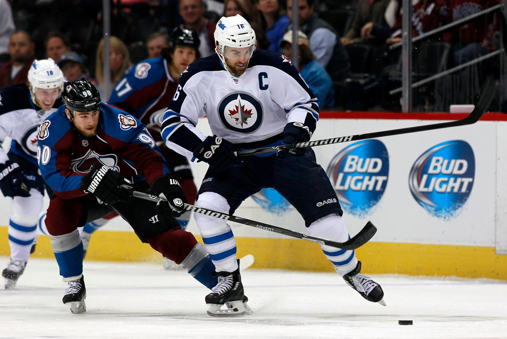 . Winnipeg Jets left wing Andrew Ladd, right, is hooked while reaching out for a puck by Colorado Avalanche center Ryan O\'Reilly in the first period of an NHL hockey game in Denver on Sunday, Oct. 27, 2013. (AP Photo/David Zalubowski)