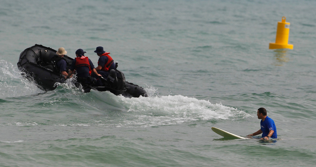 . Members of the US Coast Guard drive away after talking to a surfer near where President Barack Obama, first lady Michelle Obama, and daughters are spending their holiday vacation in Kailua, Hawaii., Friday, Dec. 25, 2009.  (AP Photo/Chris Carlson)