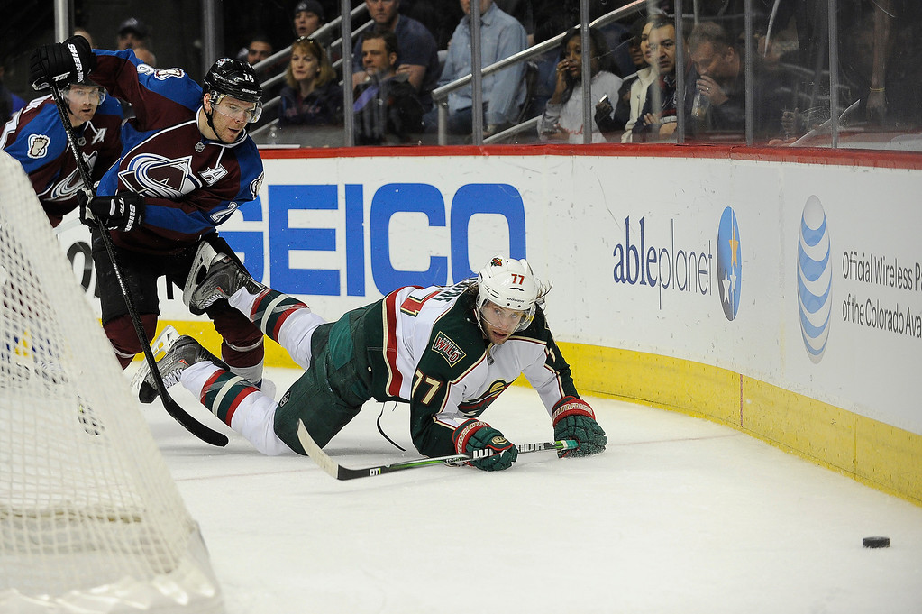 . Paul Stastny (26) of the Colorado Avalanche and Tom Gilbert (77) of the Minnesota Wild battle for the puck during the third period, Saturday, April 27, 2012 at Pepsi Center. Seth A. McConnell, The Denver Post