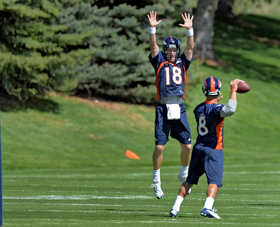 . Peyton Manning (18) of the Denver Broncos tries to distract Ryan Katz (8) as he drops back to pass during the teams OTAs May 20, 2013 at Dove Valley. All offseason training activities (OTAs) are voluntary until the mandatory minicamp June 11-13. (Photo By John Leyba/The Denver Post)