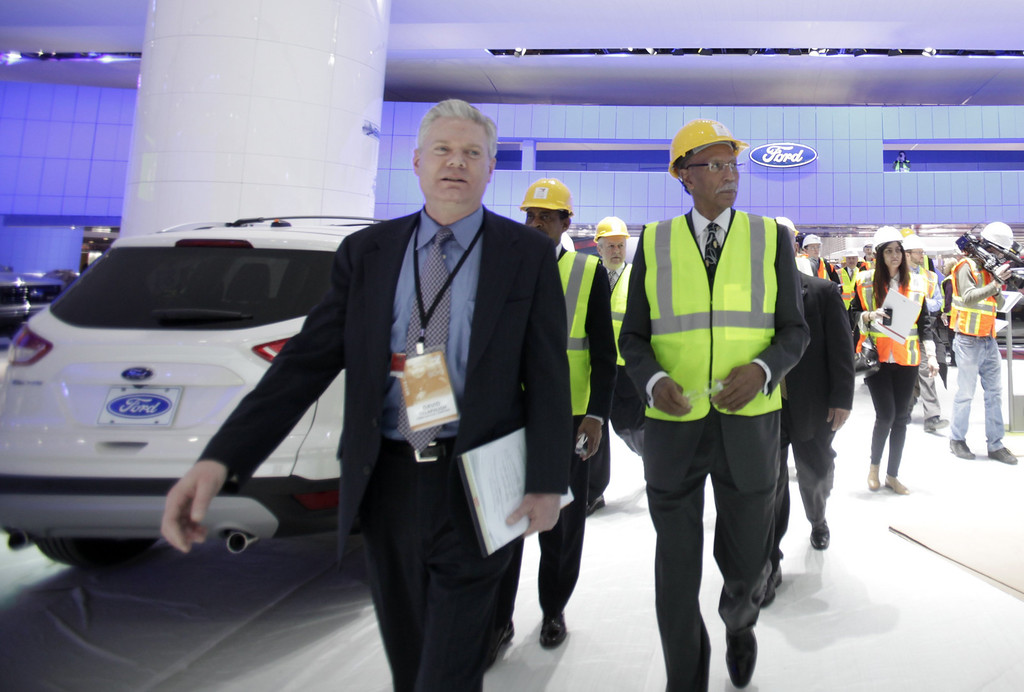 . In this Thursday, Jan. 10, 2013 photo, Ford Motor Company global auto show operations manager David Tillapaugh, foreground, walks through the Ford display with Detroit Mayor Dave Bing during an early tour of the North American International Auto Show in Detroit. (AP Photo/Detroit Free Press, Jarrad Henderson)