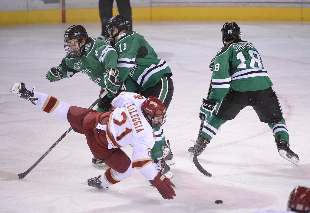. DENVER, CO. - JANUARY 24:  North Dakota defenseman Paul LaDue (6) knocked Denver defeseman Joey Laleggia (21) off the puck in the second period. The University of Denver hockey team hosted North Dakota at Magness Arena Friday night, January 24, 2014. Photo By Karl Gehring/The Denver Post