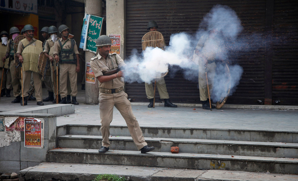 . Indian policemen fire teargas shells towards Hindus protesting against the state government after rival communities clashed in Kishtwar, in Jammu, India, Saturday, Aug. 10,2013. Indian forces fired warning shots Saturday to enforce a curfew and to push angry people back into their homes in Kishtwar, in the Indian portion of Kashmir where clashes between Muslims and Hindus during Eid celebrations killed at least two people and injured another 24.(AP Photo/Channi Anand)