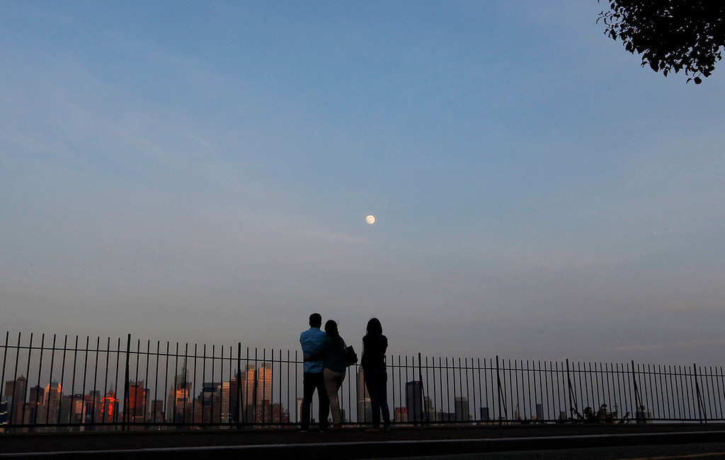 ". People watch the moon rise over the skyline of New York from a lookout in Weekhawken, New Jersey on June 21, 2013. On Saturday a perigee moon will coincide with a full moon creating a ""super moon\"" when it will pass by the earth at its closest point in 2013.  REUTERS/Gary Hershorn"