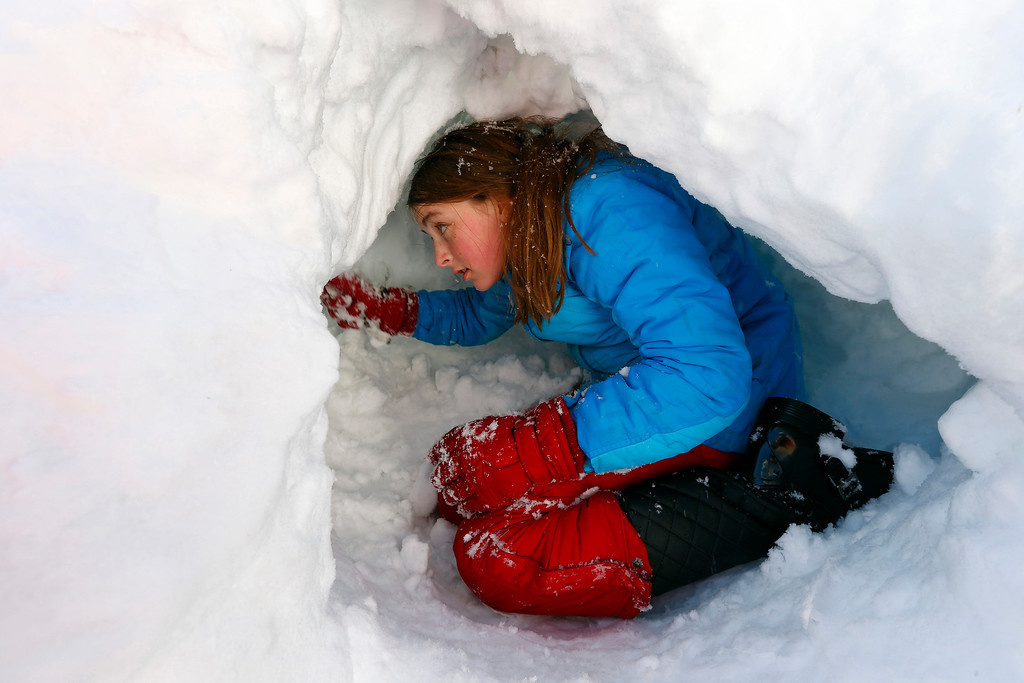 . Claire Stout, 12, burrows into a pile of plowed snow near her home in Maplewood, N.J. on Saturday, Feb. 9, 2013. The Northeast storm dumped over a foot of snow in northern N.J. (AP Photo/Rich Schultz)