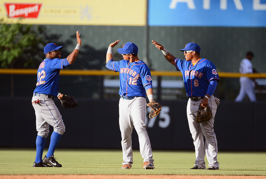 . Eric Young #22, Juan Lageres #12 and Marion Byrd #6 of the New York Mets celebrate after defeating the Colorado Rockies 3-2 at Coors Field on June 27, 2013 in Denver, Colorado. (Photo by Garrett W. Ellwood/Getty Images)