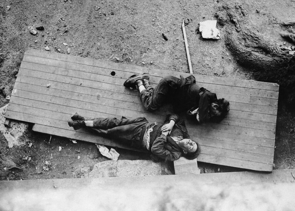 . Two men nap on a wooden slab in the Warsaw Ghetto in Poland, 1943.  (AP Photo)