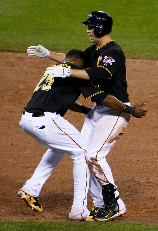 . Pittsburgh Pirates\' Jordy Mercer, right, celebrates with teammate Gregory Polanco after hitting a walk off double off Colorado Rockies relief pitcher Chad Bettis during the 11th inning of a baseball game in Pittsburgh Saturday, July 19, 2014. The Pirates won in 3-2 in 11 innings. (AP Photo/Gene J. Puskar)