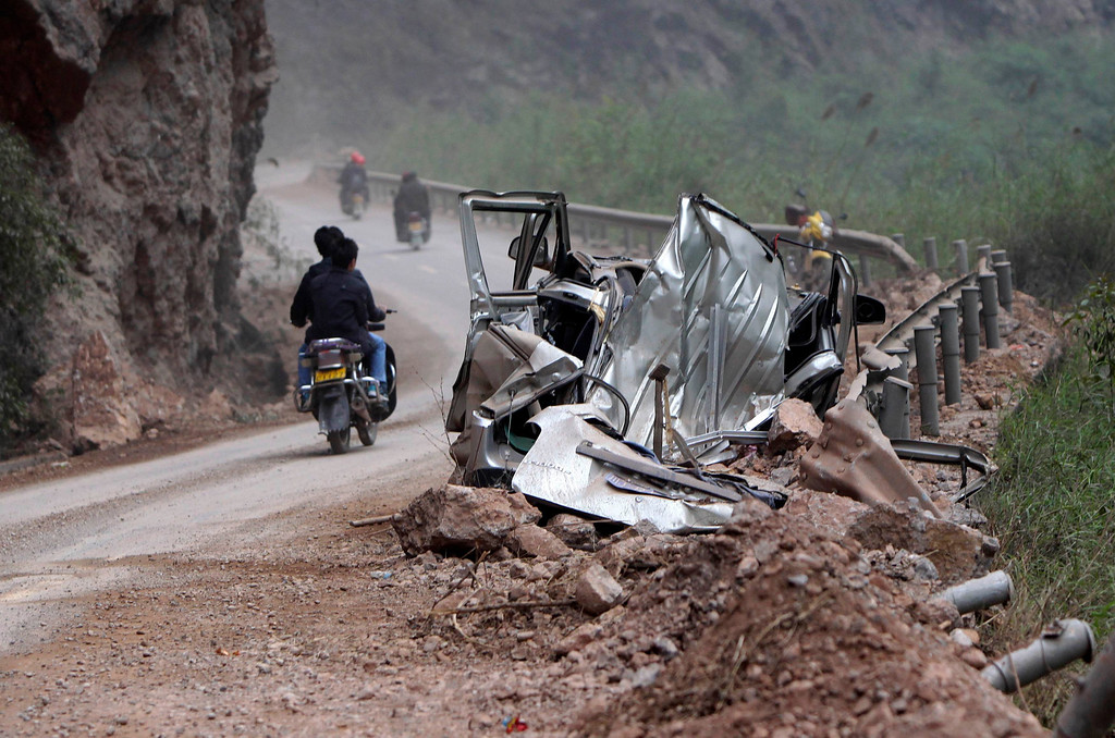 . A damaged car lies in the debris of a landslide caused by Saturday\'s earthquake on a road to Lingguan township, in Baoxing county in Ya\'an, Sichuan province April 22, 2013. REUTERS/Jason Lee