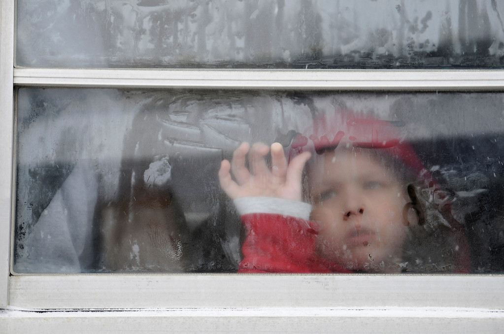 . A Sevierville Primary School student writes on a bus window as county schools let out at 10:15 a.m. due to snow and cold in Sevierville, Tenn. Tuesday Jan. 28, 2014. Snowfall across East Tennessee has led several school districts to call off classes early. (AP Photo/The Mountain Press,Curt Habraken)