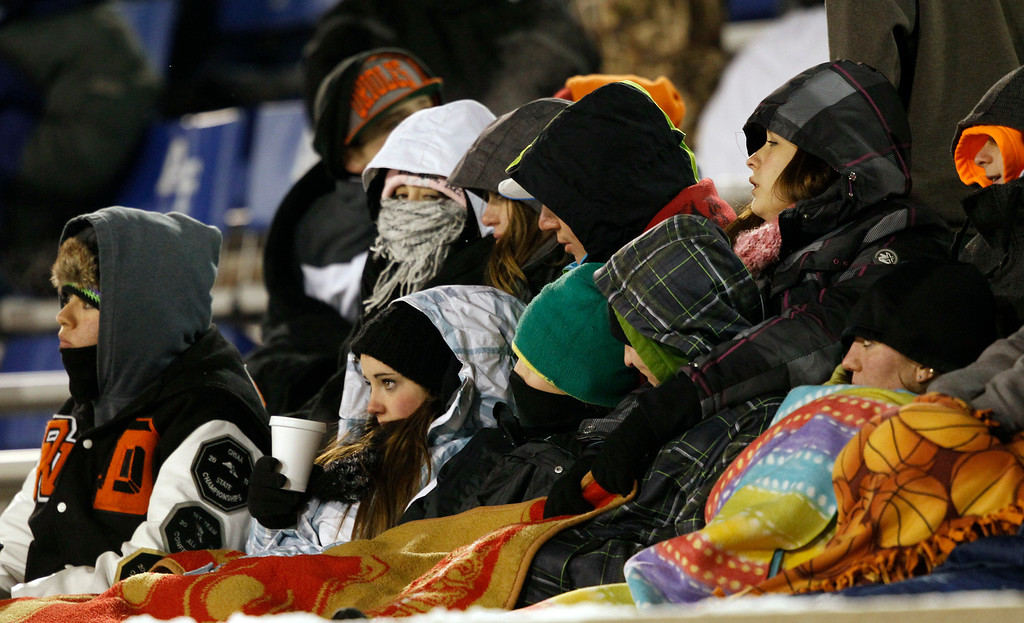 . Fans huddle together for warmth as temperatures drop into the single digits during the second quarter of an NCAA football game between UNLV and Air Force at Air Force Academy, Colo., on Thursday, Nov. 21, 2013. (AP Photo/David Zalubowski)