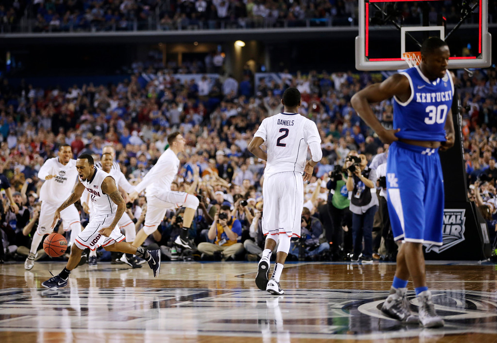 . Connecticut players, including guard Ryan Boatright (11) and forward DeAndre Daniels (2) celebrate as Kentucky forward Julius Randle (30) leaves the court at the end the NCAA Final Four tournament college basketball championship game Monday, April 7, 2014, in Arlington, Texas. Connecticut won 60-54. (AP Photo/David J. Phillip)