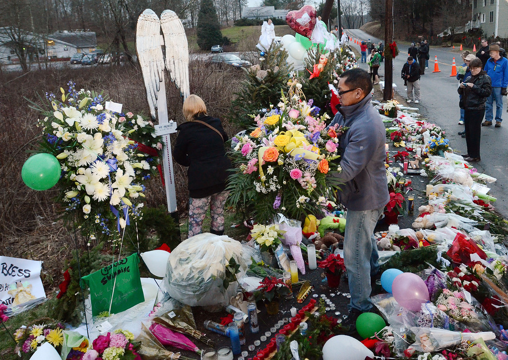 . Staff photos by Tom Kelly IV Mourners gather at the memorial, near the entrance to the Sandy Hook Elementary School.  Funerals for two, six year old students from the Sandy Hook Elementary School in Newtown, CT took part Tuesday December 18, 2012.  Mourners paid their respects at the Saint Rose of Lima Church.