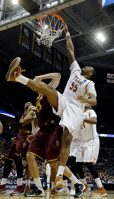. Texas center Cameron Ridley (55) grabs on to the rim as he misses a dunk against Arizona State center Jordan Bachynski (13) during the second half of a second-round game in the NCAA college basketball tournament Thursday, March 20, 2014, in Milwaukee. (AP Photo/Morry Gash)