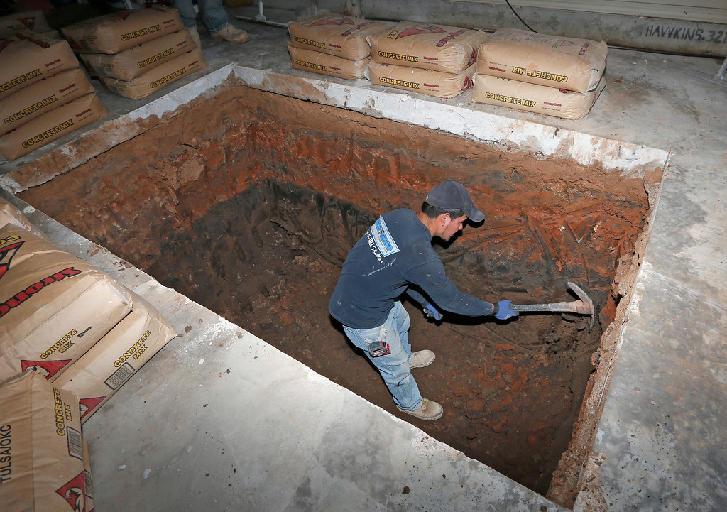 . In this Thursday, May 1, 2014 photo, Jacob Ortiz, of Thunderground Storm Shelters, puts the finishing touches on a hole for a storm shelter installation in the garage of a residence in Oklahoma City. (AP Photo/Sue Ogrocki)