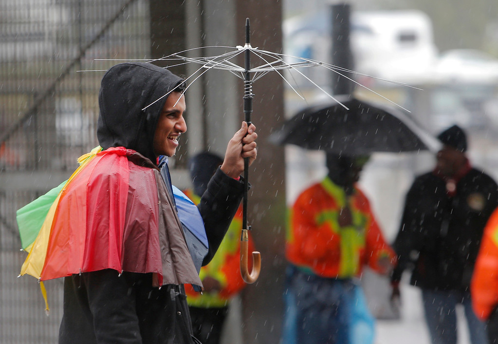 . A young man  holds a broken umbrella outside of the memorial service of Nelson Mandela at  the FNB stadium in  Johannesburg, South Africa, Tuesday, Dec. 10, 2013. Mandela died Thursday at his Johannesburg home after a long illness. He was 95. (AP Photo/Tsvangirayi Mukwazhi)