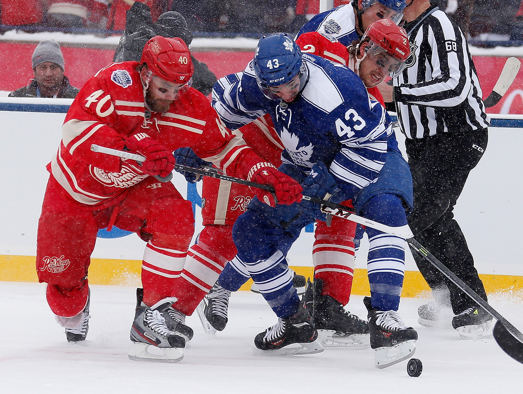 . Henrik Zetterberg #40 and Brendan Smith #2 of the Detroit Red Wings fight for the puck with Nazem Kadri #43 of the Toronto Maple Leafs during the first period of the 2014 Bridgestone NHL Winter Classic at Michigan Stadium on January 1, 2014 in Ann Arbor, Michigan. (Photo by Gregory Shamus/Getty Images)