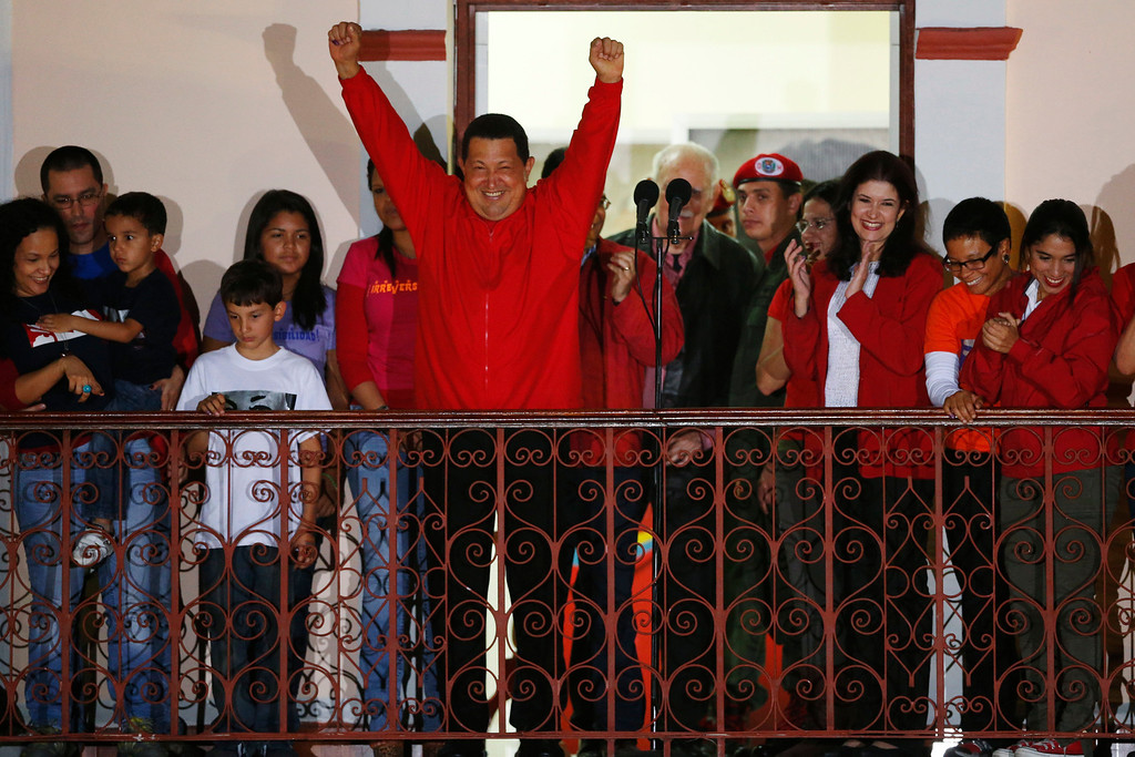 . Venezuelan president Hugo Chavez celebrates from people\'s balcony at Miraflores Palace in Caracas October 7, 2012. Venezuela\'s socialist President Hugo Chavez won re-election in Sunday\'s vote with 54 percent of the ballot to beat opposition challenger Henrique Capriles.   REUTERS/Jorge Silva