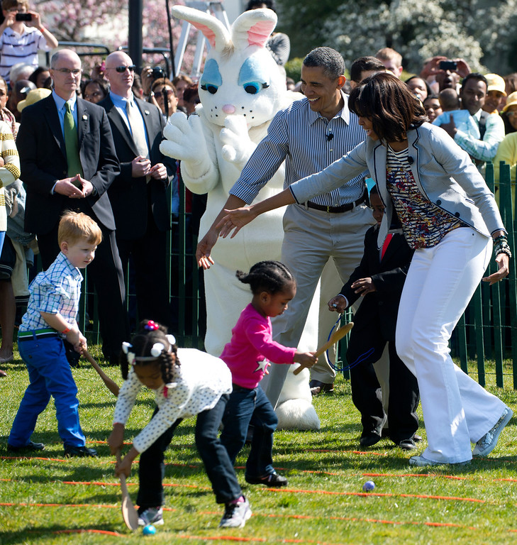 . US President Barack Obama and First Lady Michelle Obama cheer on as children race to roll eggs as they participate in the White House Easter Egg Roll on the South Lawn of the White House in Washington, DC, April 1, 2013. Obama hosts the annual event, featuring live music, sports courts, cooking stations, storytelling and Easter egg rolling. AFP PHOTO / Saul L LOEB/AFP/Getty Images