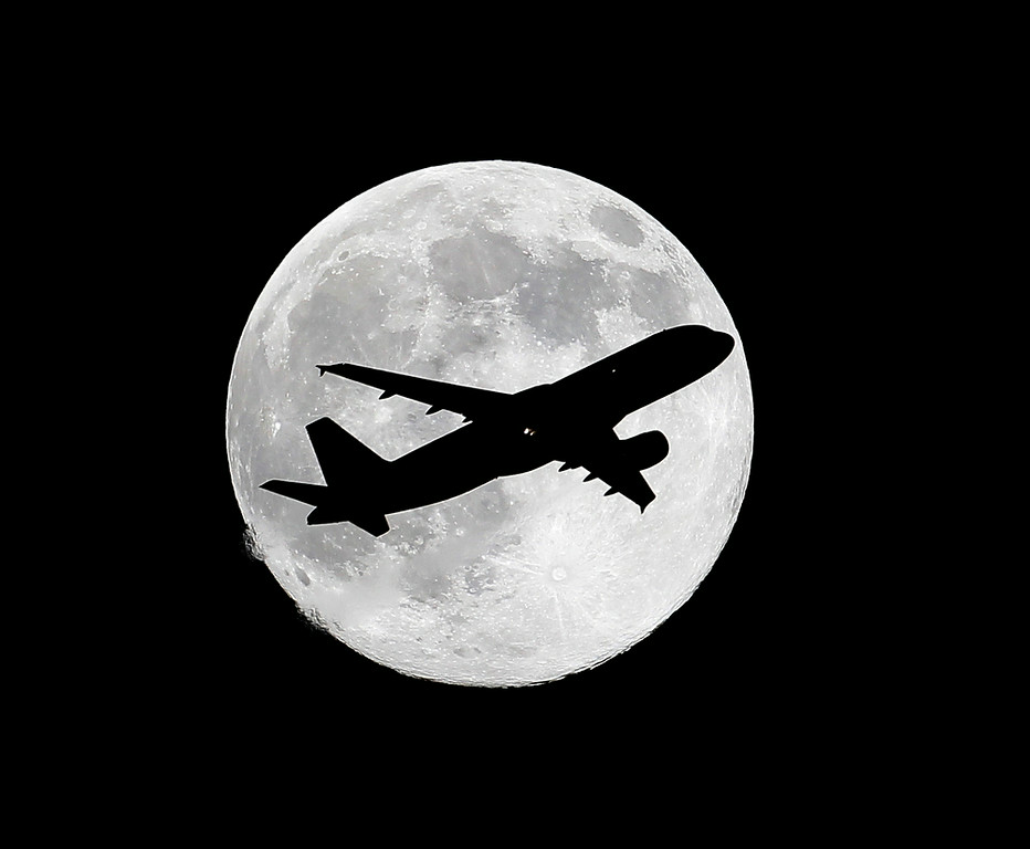 ". One day before the ""supermoon,\"" a commercial airliner crosses the waxing gibbous moon on its final approach to Los Angeles Airport as viewed from Whittier, Calif., Friday, July 11, 2014. (AP Photo/Nick Ut)"