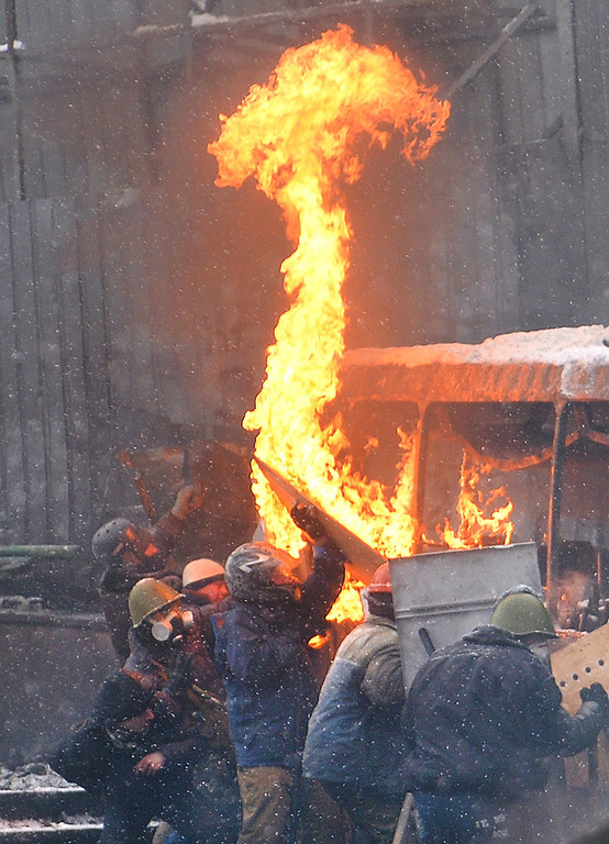 . Protesters hide themselves behind the wreckage of a bus during clashes with riot police in the center of Kiev on January 22, 2014. AFP PHOTO/ SERGEI SUPINSKY/AFP/Getty Images