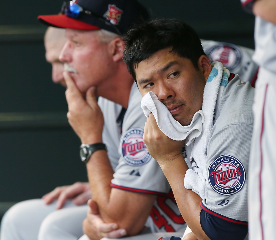 . Minnesota Twins catcher Kurt Suzuki looks on from dugout against the Colorado Rockies in the eighth inning of the Twins\' 13-5 victory in an interleague baseball game in Denver on Sunday, July 13, 2014. (AP Photo/David Zalubowski)