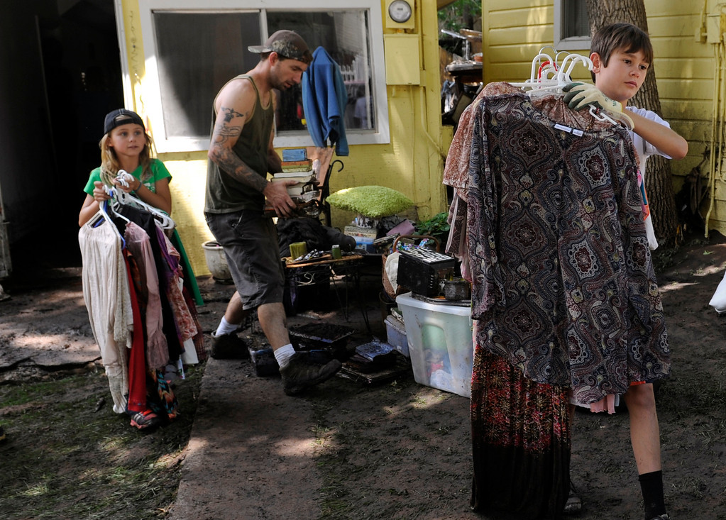. MANITOU SPRINGS, CO - Aug.10: Joah Armour, 10, right, leads the way as he helps remove clothing from the rental home of a mother and her daughter. Armour joined his parents and residents and crews clean up the damage and debris along Canon Avenue after a flash flood roared through the streets and hillsides on Friday evening. (Photo By Kathryn Scott Osler/The Denver Post)