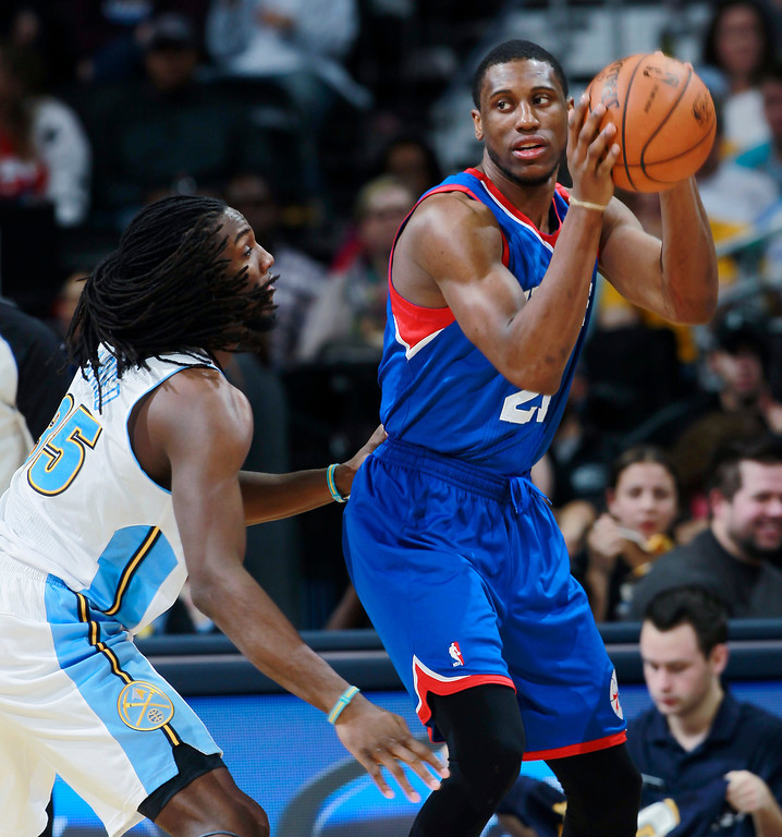 . Philadelphia 76ers forward Thaddeus Young, right, looks to pass the ball as Denver Nuggets forward Kenneth Faried defends during the third quarter of the Sixers\' 114-102 victory in an NBA basketball game in Denver on Wednesday, Jan. 1, 2014. (AP Photo/David Zalubowski)