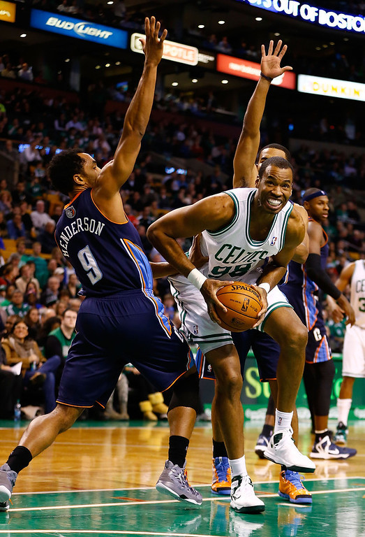 . Jason Collins #98 of the Boston Celtics splits the defenders underneath the basket in front of Gerald Henderson #9 of the Charlotte Bobcats during the game on January 14, 2013 at TD Garden in Boston, Massachusetts. (Photo by Jared Wickerham/Getty Images)