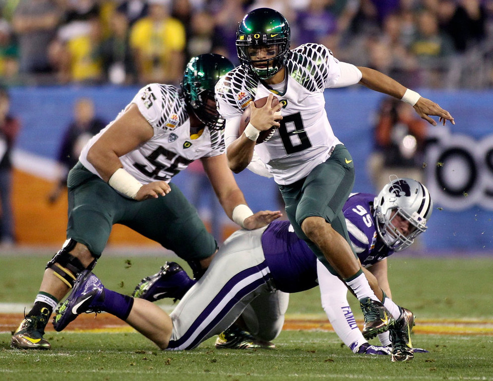 . Oregon Ducks quarterback Marcus Mariota (8) gets away from Kansas State Wildcats defensive lineman Travis Britz (95) during the Fiesta Bowl football game in Glendale, Arizona, January 3, 2013. REUTERS/Ralph Freso
