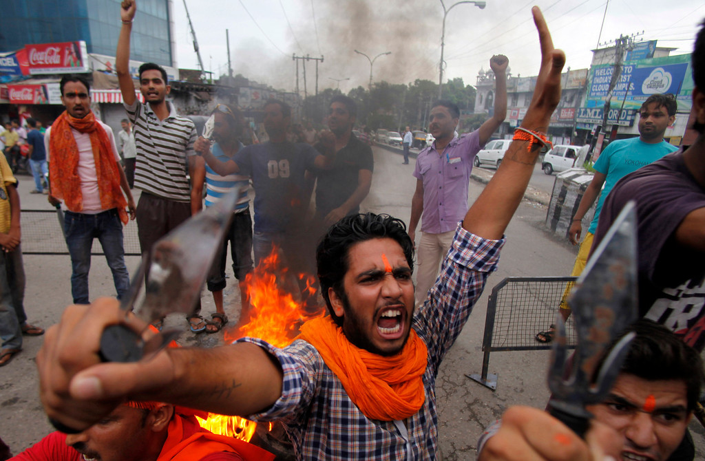 . A Hindu protestor shouts slogans against the state government after rival communities clashed in Kishtwar, in Jammu, India, Saturday, Aug. 10, 2013. Indian forces fired warning shots Saturday to enforce a curfew and to push angry people back into their homes in Kishtwar, in the Indian portion of Kashmir where clashes between Muslims and Hindus during Eid celebrations killed at least two people and injured another 24. (AP Photo/Channi Anand)