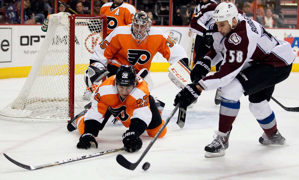 . Philadelphia Flyers\' Luke Schenn, left, and Colorado Avalanche\' Patrick Bordeleau, right, reach for the loose puck while goalie Steve Mason looks on during the first period of an NHL hockey game, Thursday, Feb. 6, 2014, in Philadelphia. (AP Photo/Tom Mihalek)