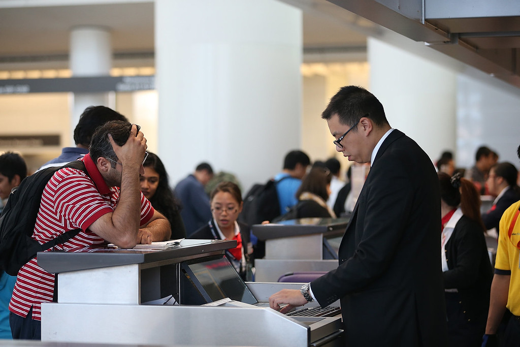 . A traveler speaks to an airline ticket agent in the international terminal at San Francisco International Airport on July 7, 2013 in San Francisco, California. A day after Asiana Airlines flight 214 crashed upon landing at San Francisco International Airport, stranded travelers are experiencing long lines and cancelled flights as the airport continues to operate with only two runways for departures and arrivals. Two people died and dozens were injured in the crash that shut down the airport for several hours and resulted in dozens of flights being cancelled.  (Photo by Justin Sullivan/Getty Images)