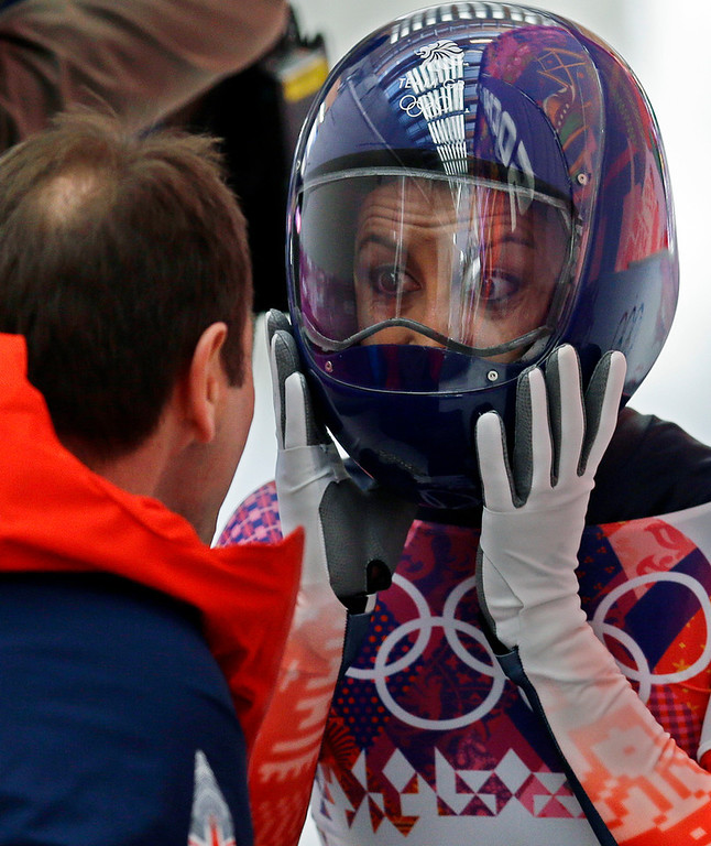 . Shelley Rudman of Great Britain speaks to her coach in the finish area after her first run during the women\'s skeleton competition at the 2014 Winter Olympics, Thursday, Feb. 13, 2014, in Krasnaya Polyana, Russia. (AP Photo/Natacha Pisarenko)