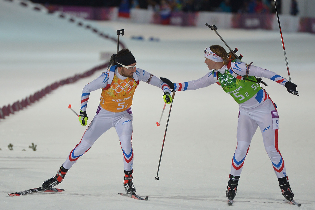 . France\'s Anais Bescond hands over to team mate Jean Guillaume Beatrix as they compete in the Biathlon mixed 2x6 km + 2x7,5 km Relay at the Laura Cross-Country Ski and Biathlon Center during the Sochi Winter Olympics on February 19, 2014 in Rosa Khutor near Sochi.  AFP PHOTO / ALBERTO PIZZOLI/AFP/Getty Images