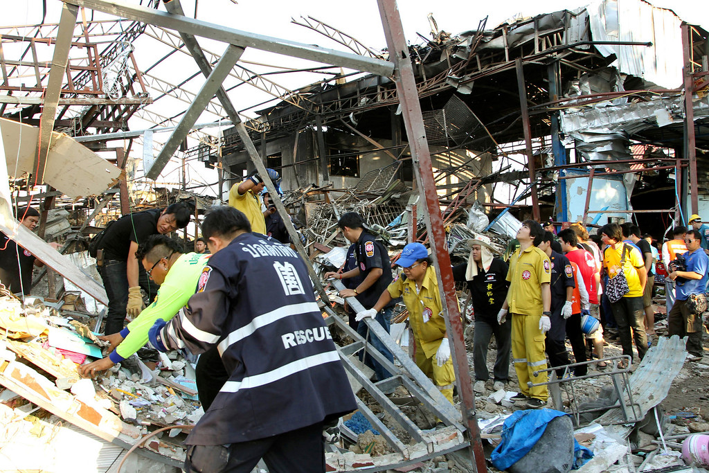 . Thai charity workers sift through the wreckage of a scrap shop after a bomb explosion in Bangkok, Thailand Wednesday, April 2, 2014. (AP Photo/Apichart Weerawong)
