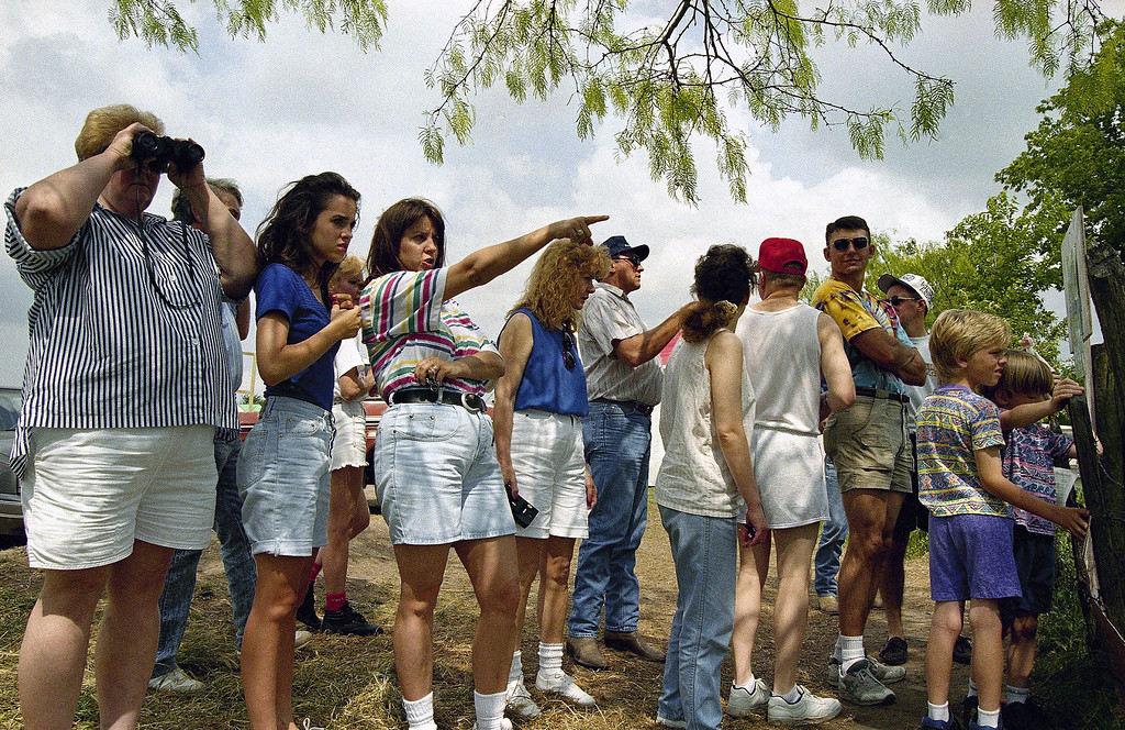 . A group of people gather on a hillside and look toward the site where the Branch Davidian compound once stood about 6 miles away outside of Waco, Texas on Sunday, April 25, 1993. The hillside, outside of Waco, Texas, has been a popular place for the curious, after the Bureau of Alcohol, Tobacco and Firearms raid on February 28.  (AP Photo/Roberto Borea)
