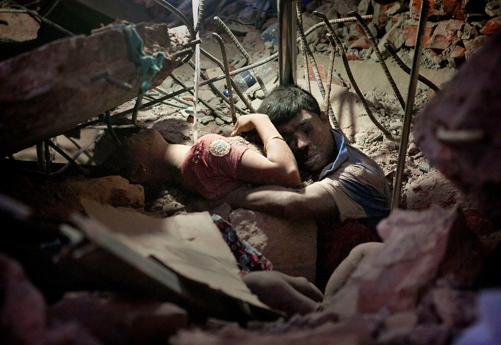 . A Bangladeshi man holds on to a woman, both victims of a building collapse, in the debris of Rana Plaza garment factory in Savar near Dhaka, Bangladesh, April 25, 2013. The collapse of Rana Plaza in Dhaka that killed 1,129 people.  (AP Photo/Suman Paul)