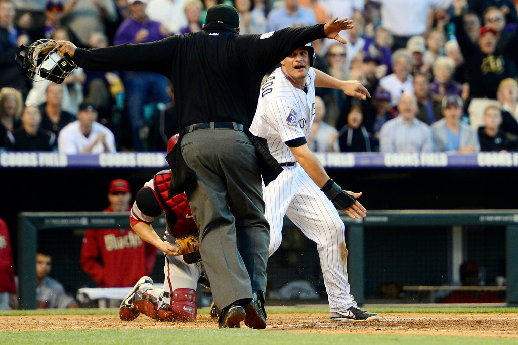 . DENVER, CO - MAY 21: Nolan Arenado (28) of the Colorado Rockies is called safe at the plate after sliding under the tag of Miguel Montero (26) of the Arizona Diamondbacks during action at Coors Field. The Arizona Diamondbacks visited the Colorado Rockies. (Photo by AAron Ontiveroz/The Denver Post)