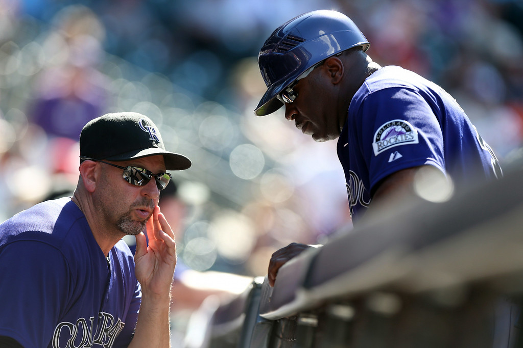 . Colorado Rockies manager Walt Weiss, left, confers with first base coach Eric Young while facing the San Francisco Giants in the sixth inning of a baseball game in Denver, Wednesday, Sept. 3, 2014. The Rockies won 9-2. (AP Photo/David Zalubowski)