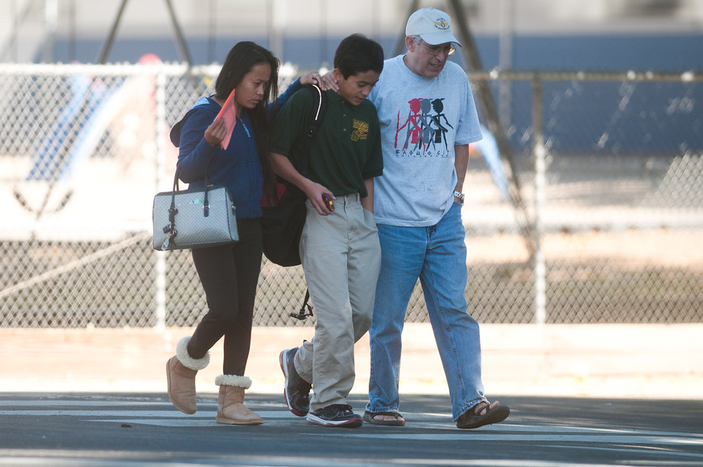 . Parents escort a child from Agnes Risley Elementary school following a shooting at nearby Sparks Middle School October 21, 2013 in Sparks, Nevada. A staff member was killed and two students were injured after a student opened fire at the Nevada middle school. The suspected gunman was also killed. Students from the middle school were evacuated and held for parents at the elementary school.  (Photo by David Calvert/Getty Images)