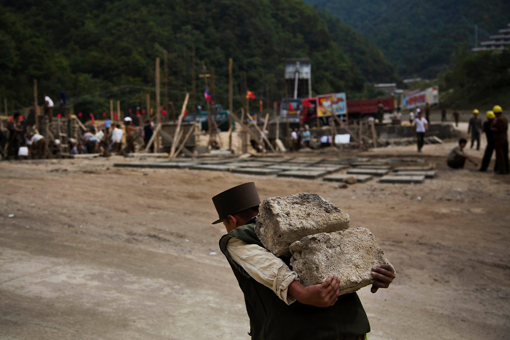""". A North Korean construction worker carries bricks at a building project to construct a ski resort at North Korea\'s Masik Pass on Friday Sept. 20, 2013. North Korean authorities have been encouraging a broader interest in sports and recreation in the country, calling it \""""the hot wind of sports blowing through Korea.\""""   (AP Photo/David Guttenfelder)"""