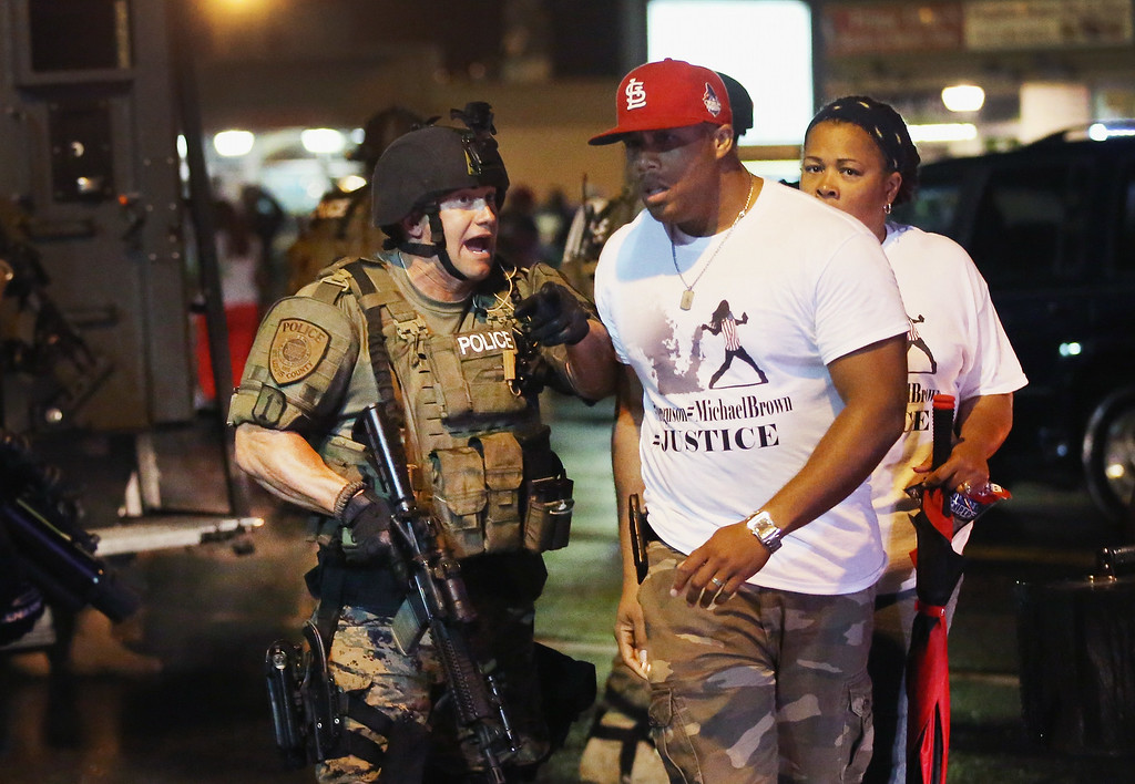 . FERGUSON, MO - AUGUST 15:  Police confront demonstrators during a protest over the shooting of Michael Williams on August 15, 2014 in Ferguson, Missouri.  County police shot pepper spray, smoke, gas and flash grenades at protestors before retreating. Several businesses were looted as county police watched from their armored personnel carriers (APC) parked nearby. Violent outbreaks have taken place in Ferguson since the shooting death of Brown by a Ferguson police officer on August 9.  (Photo by Scott Olson/Getty Images)