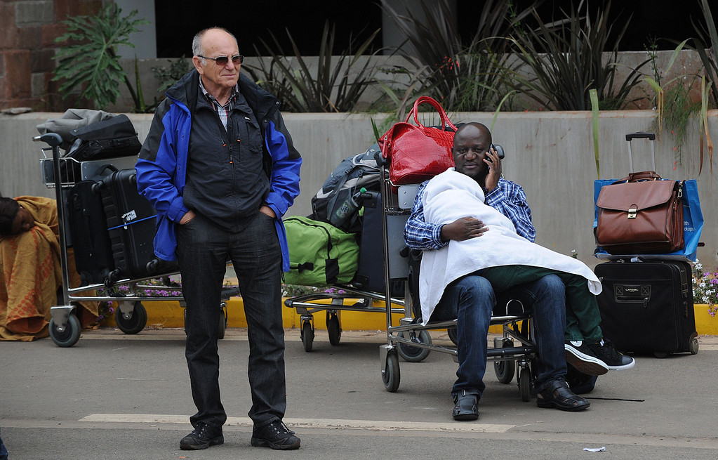 . Stranded passenger wait outside the Jomo Kenyatta International Airport in Nairobi on August 7, 2013 as a massive fire shut down Nairobi\'s international airport today with flights diverted to regional cities as firefighters battled to put out the blaze in east Africa\'s biggest transport hub.  AFP PHOTO / SIMON  MAINA/AFP/Getty Images