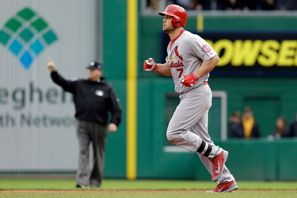 . St. Louis Cardinals\' Matt Holliday, right, jogs past second base umpire Paul Nauert as he gives the home run signal in the sixth inning of Game 4 of a National League division baseball series against the Pittsburgh Pirates on Monday, Oct. 7, 2013 in Pittsburgh. (AP Photo/Gene J. Puskar)
