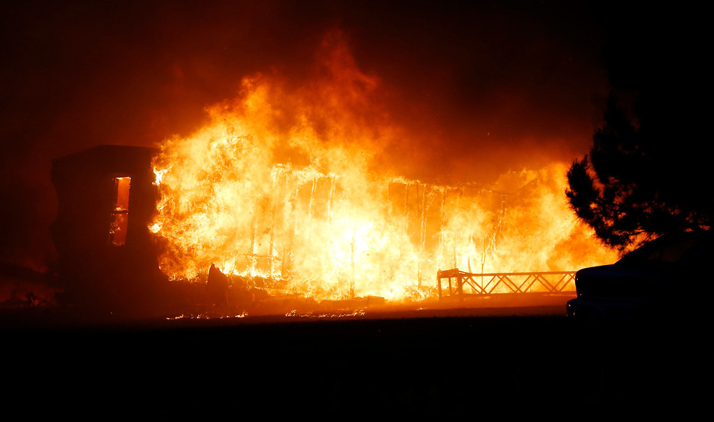 . A mobile home burns at a mobile home park near Prairie Grove and Douglas during Oklahoma wildfires in south Logan County, Sunday, May 4, 2014. Firefighters worked through the night and into early Monday to battle the large wildfire that destroyed at least six homes and left at least one person dead after a controlled burn spread out of control in central Oklahoma. (AP Photo/The Oklahoman, Nate Billings)